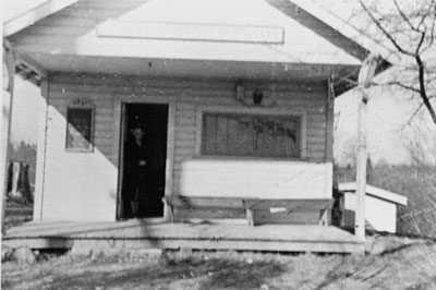 Above is the old logging camp building donated to be used as the library that burned in Nov. 1941. The librarian standing in the door is Mrs. Hildreth Engler who was the librarian at the time. She circulated books from her house until the new library opened in May 1942. Photographer: Bob Downing (One of Mrs. Engler's young patrons). Photograph Courtesy of the Photograph courtesy of the Alderwood Manor Heritage Association, circa 1940.